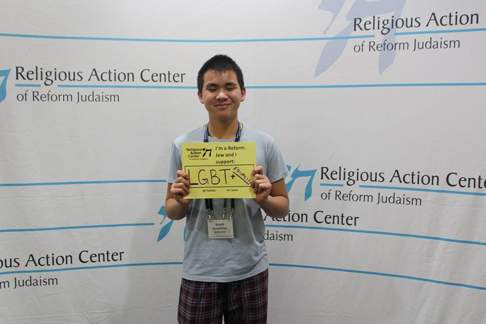 Noah Hung Spanding-Schechter with a sign that says I'm a Reform Jew and I support LGBTQ equality