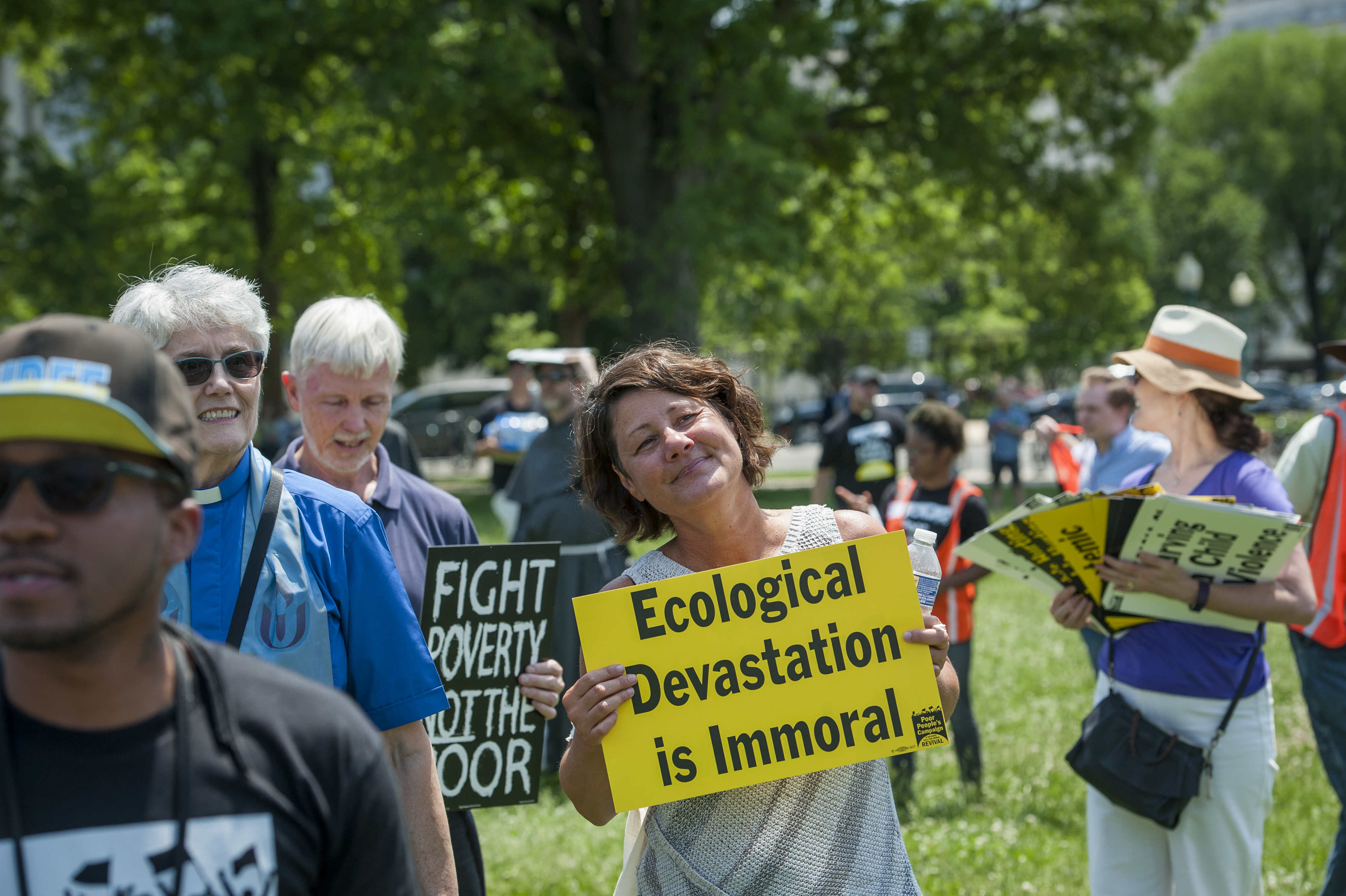 "Woman carrying sign that reads ""Ecological Devastation is Immoral"""