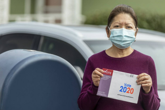 Woman wearing a face mask and holding a mail in ballot while standing next to a USPS mailbox