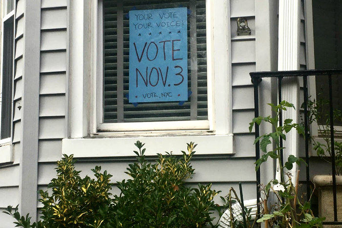 Handmade sign in a home window encouraging New Yorkers to vote on Nov 3