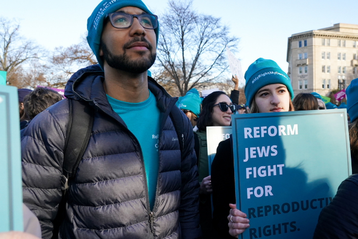 "Two people standing, holding a sign that says ""Reform Jews Fight for Reproductive Rights"""