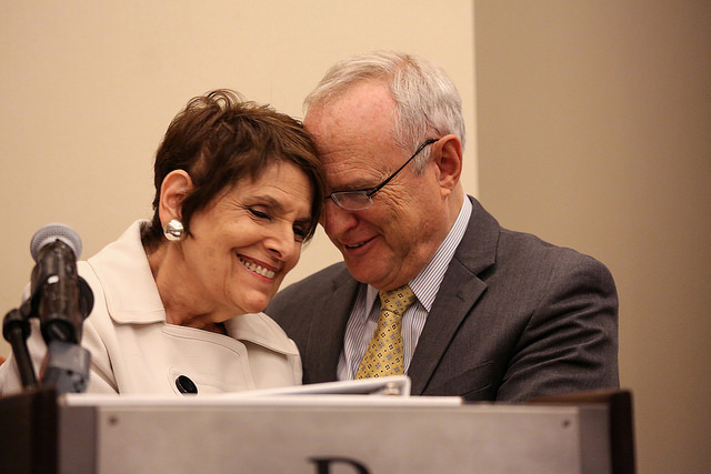 Rabbis Lynne Landsberg and David Saperstein share a moment at a podium, both smiling, heads leaned towards one another.