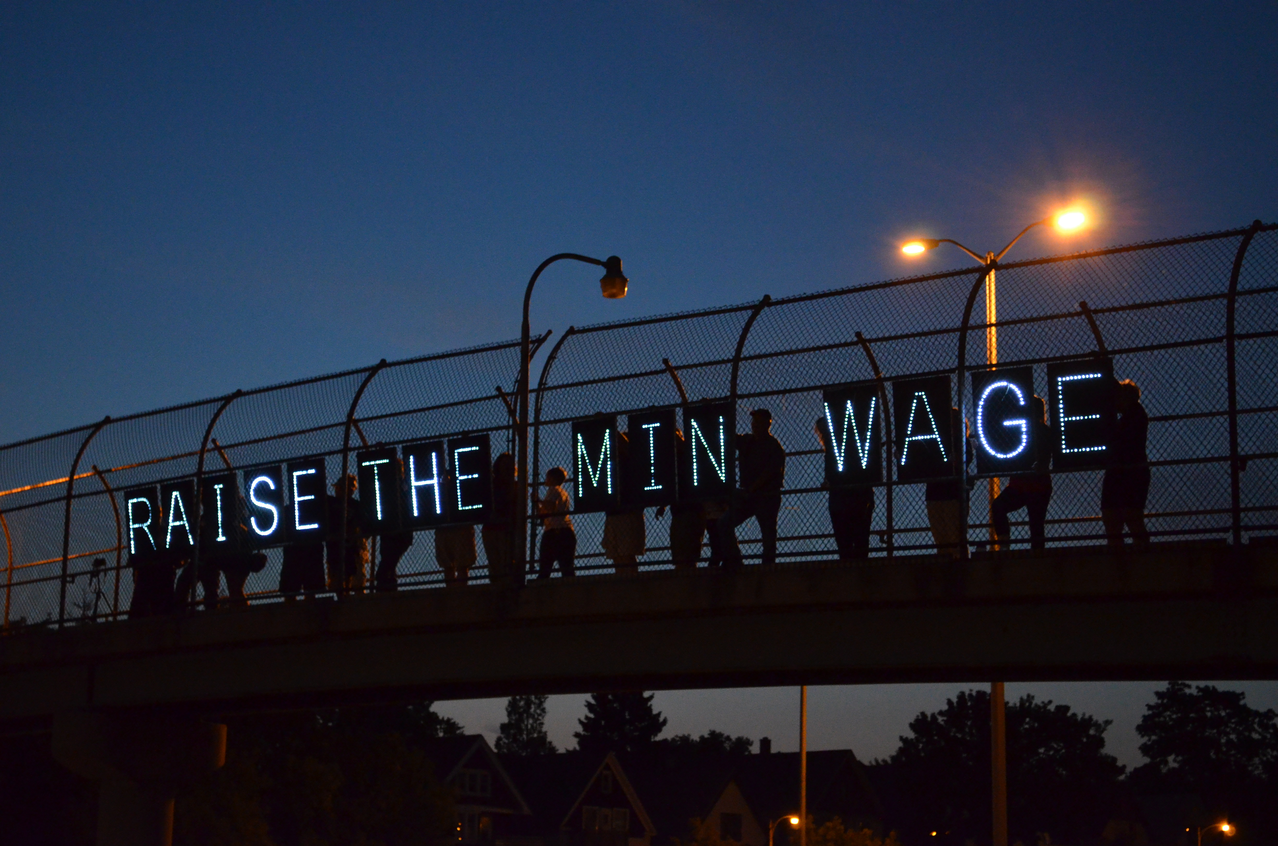 Raise the Wage sign on a bridge