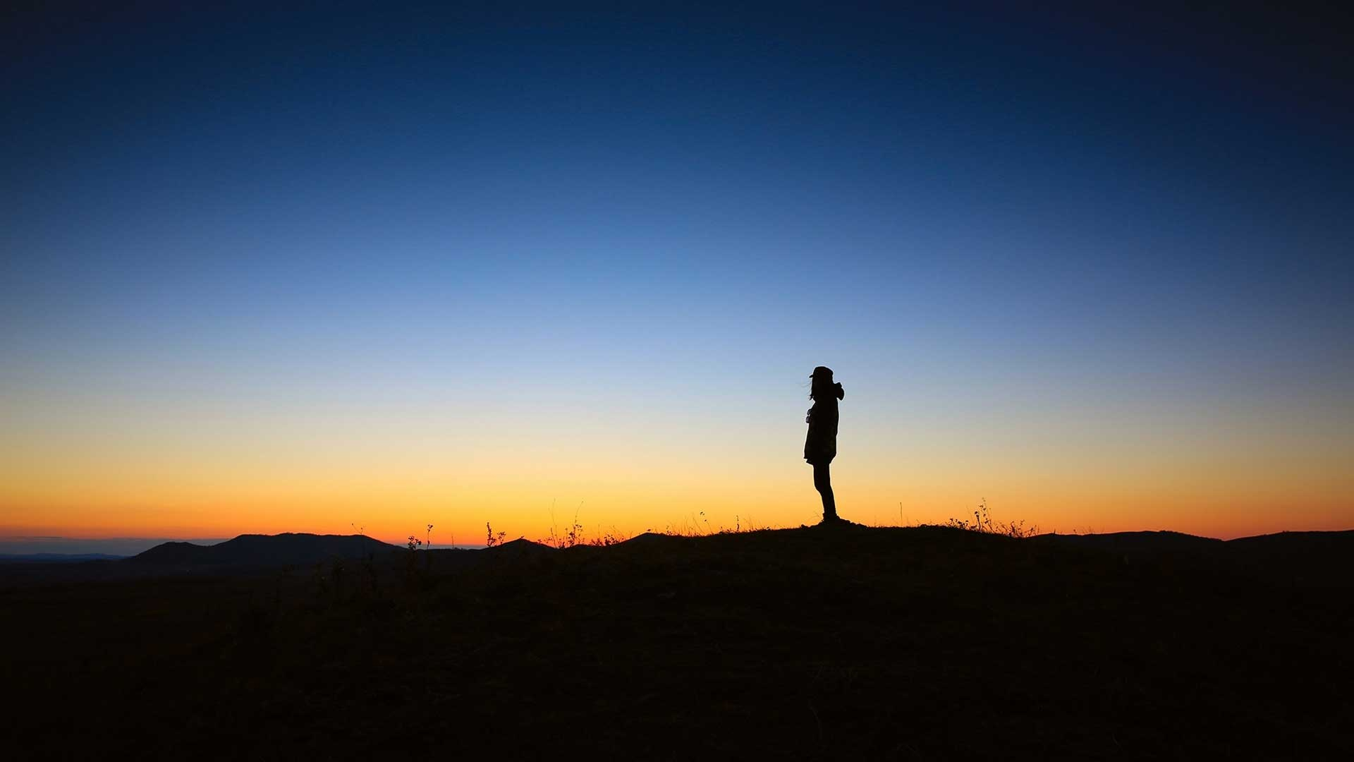 Silhouette on a mountain at sunset