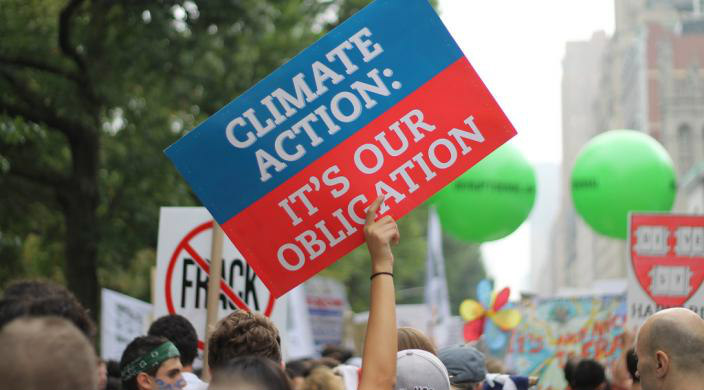 Hand holding up a sign that reads Climate Action Is Our Obligation at a protest rally