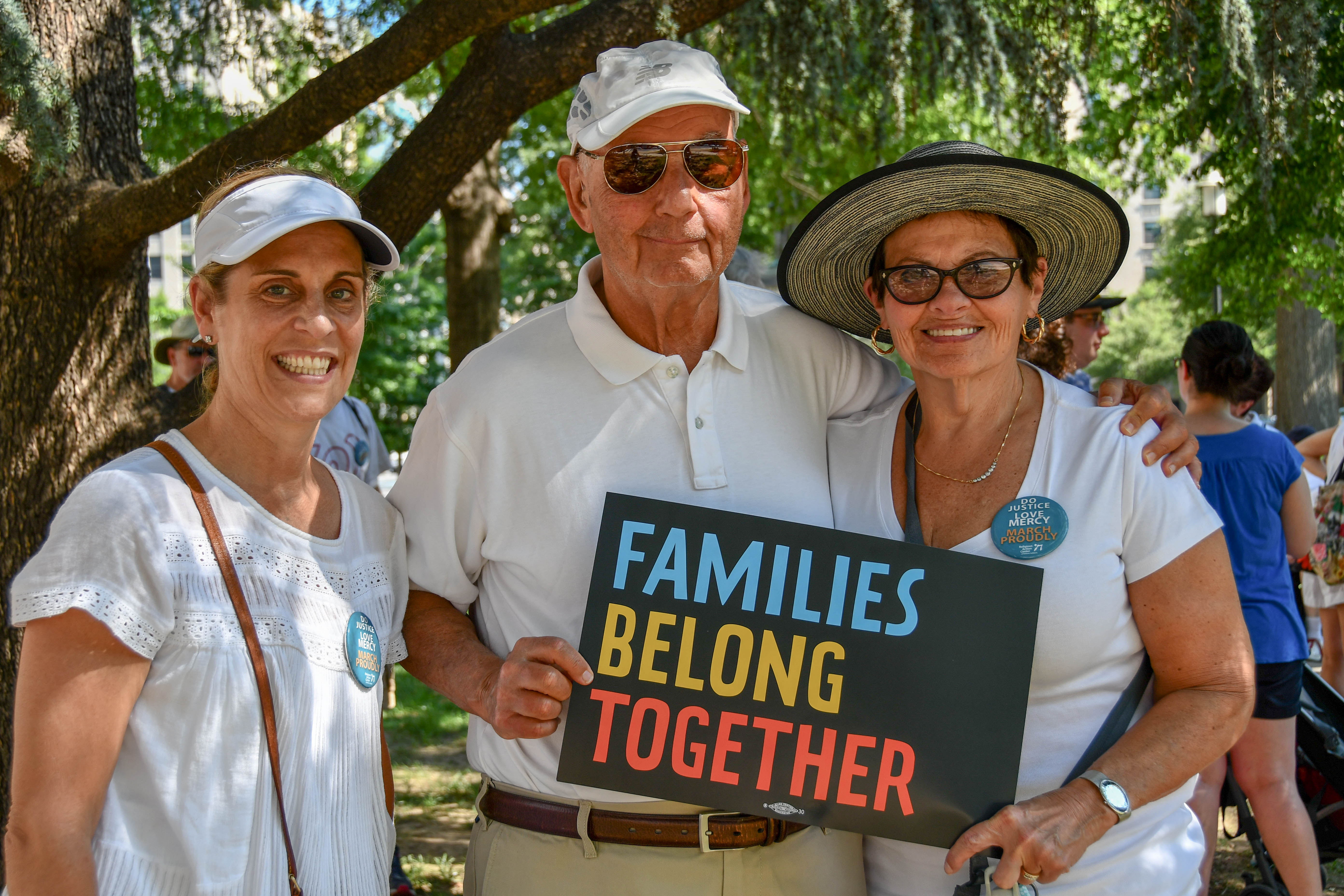"Three protesters in white with a ""Families Belong Together"" sign"