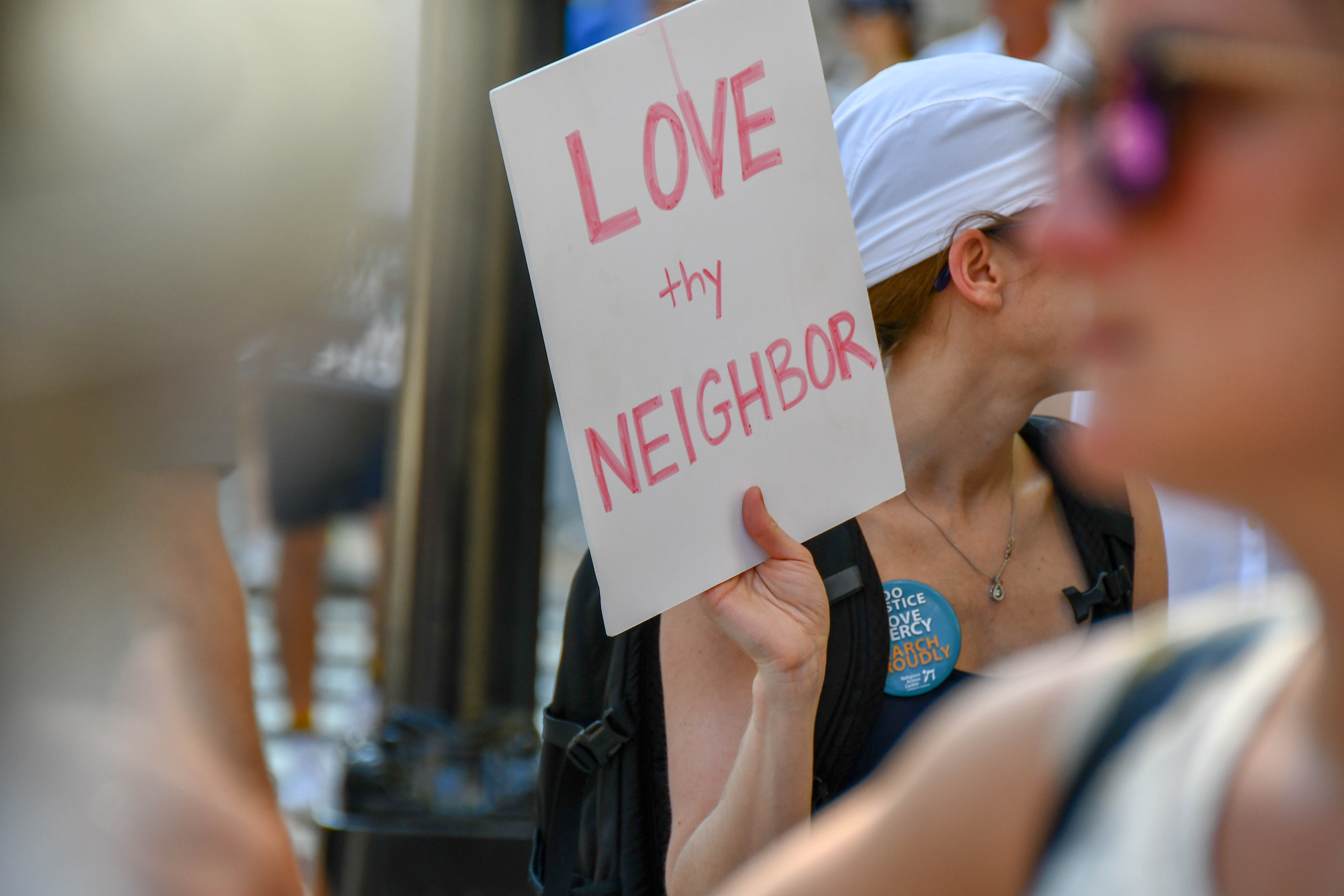 "Sign reading ""Love Thy Neighbor"" held up against a blurred green background, at a protest"