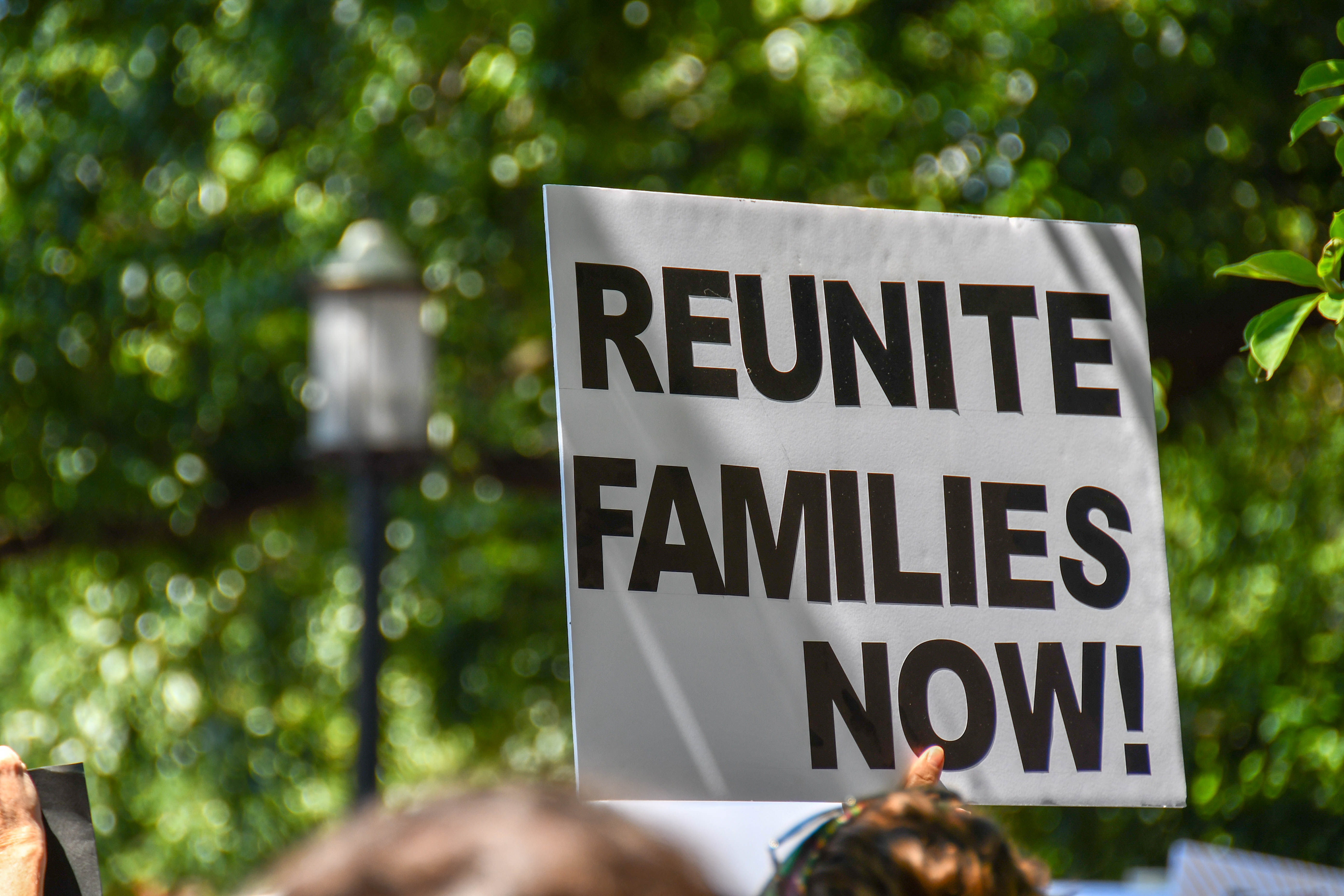 White sign with black text that reads: Reunite Families Now!