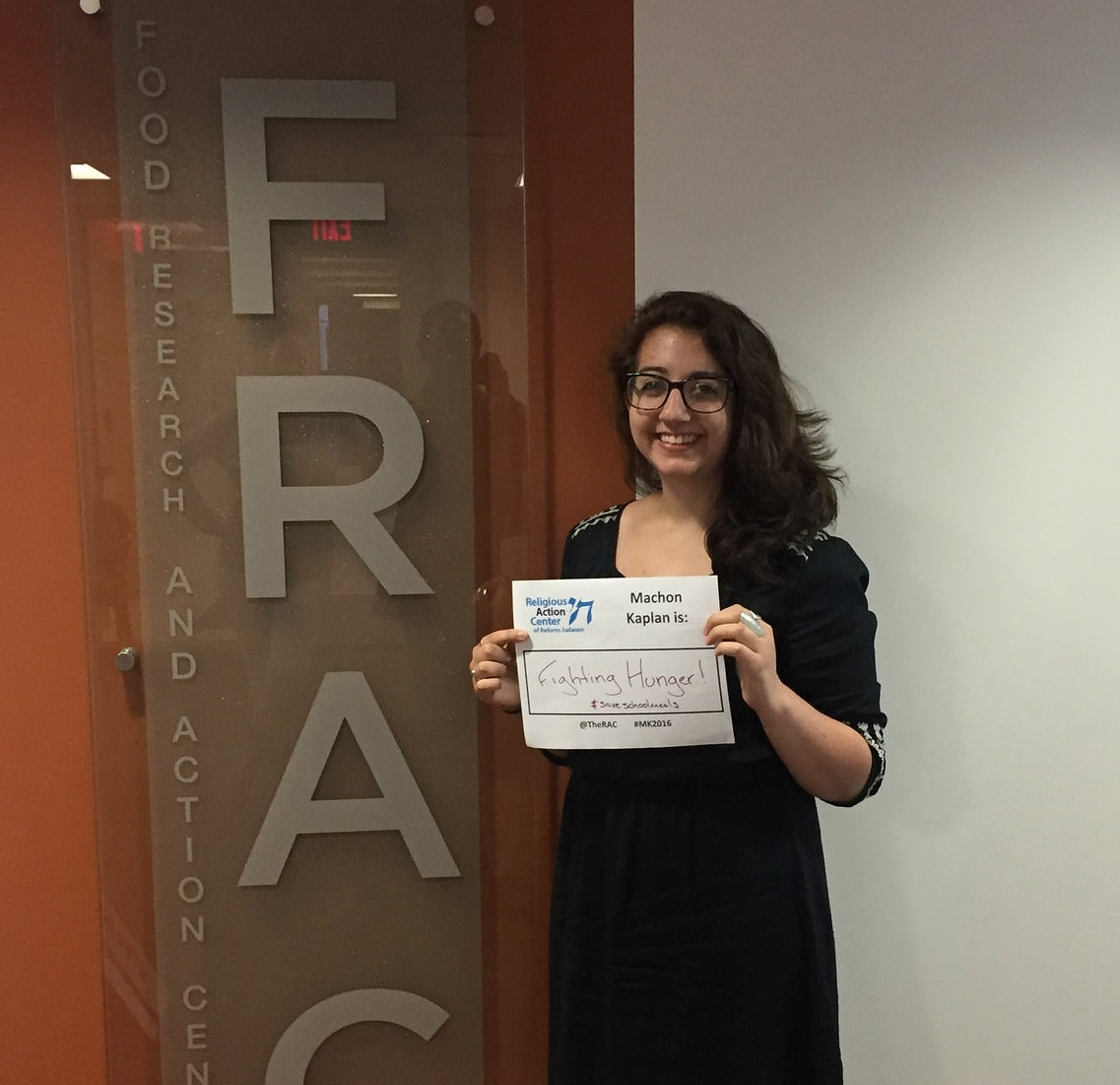 Ilana Symons in front of FRAC sign with MK is sign
