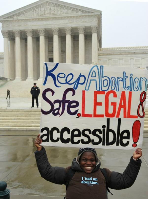 woman holding sign in front of supreme court about legal abortion