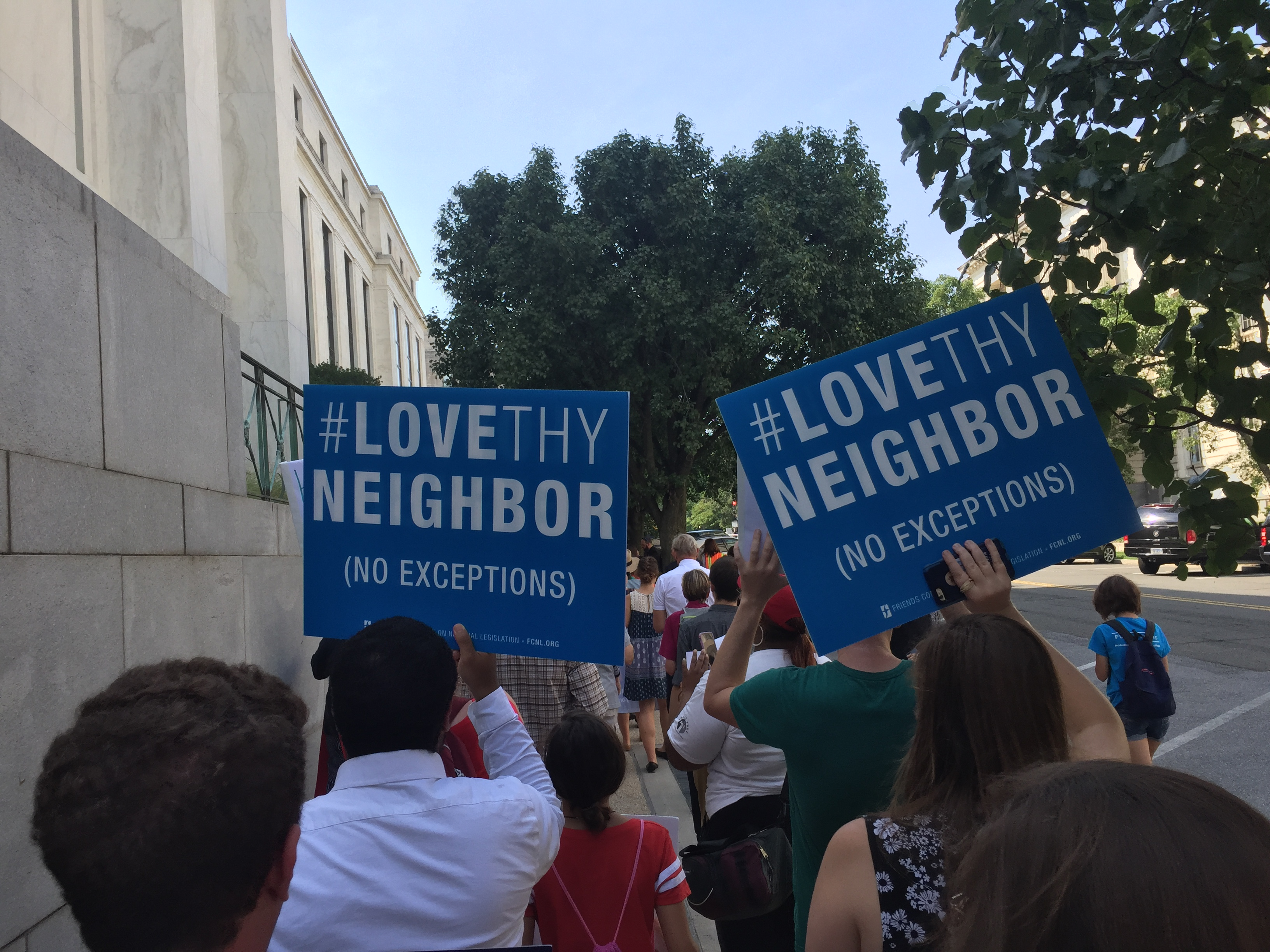 People marching with Love Thy Neighbor signs
