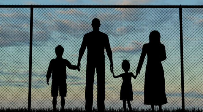 Silhouette of family members holding hands in front of a chain link fence