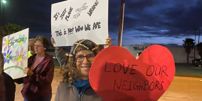 "Woman holding ""love our neighbors"" sign"