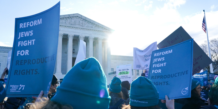 "People holding signs outside of the Supreme Court that say ""Reform Jews Fight for Reproductive Rights"""