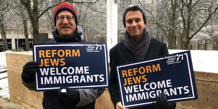 "Two men holding signs that say ""Reform Jews Welcome Immigrants"""