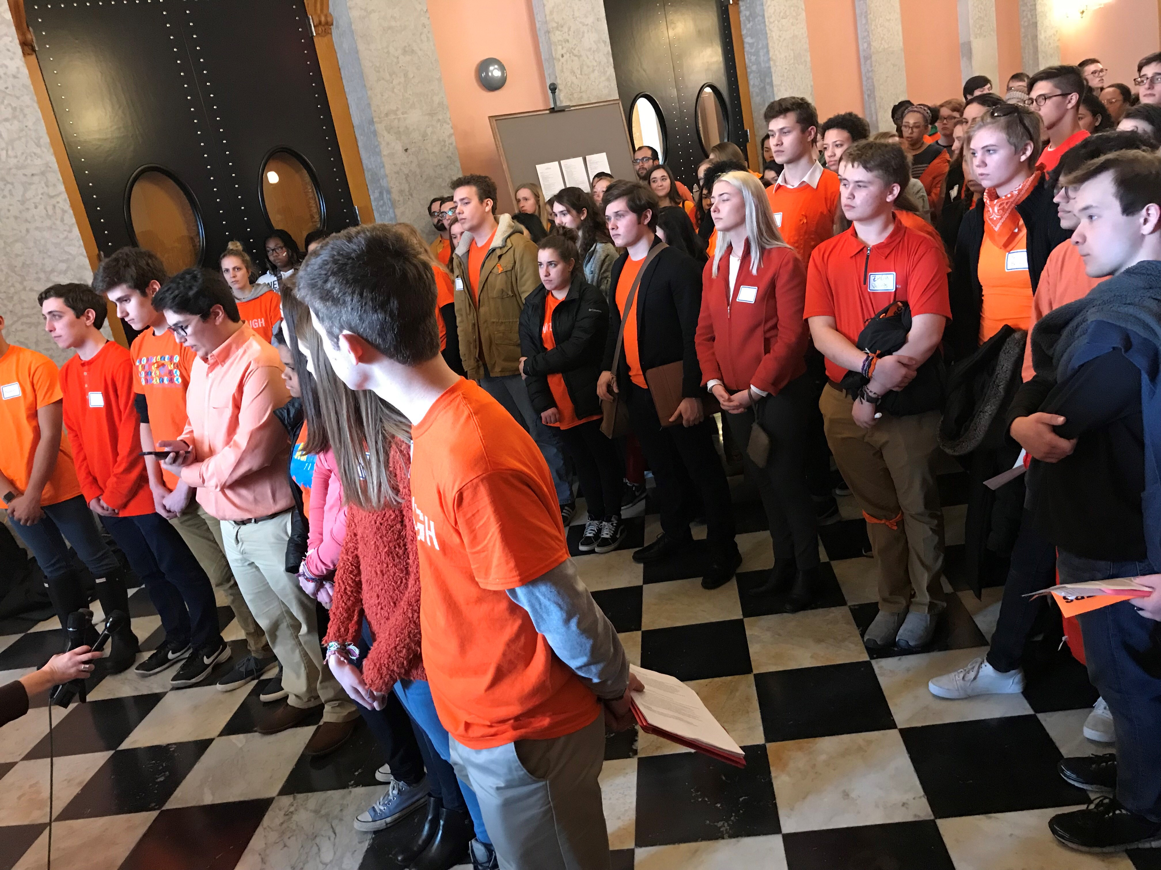 Ohio students, wearing orange for gun violence, speak to press and onlookers at the Columbus Statehouse