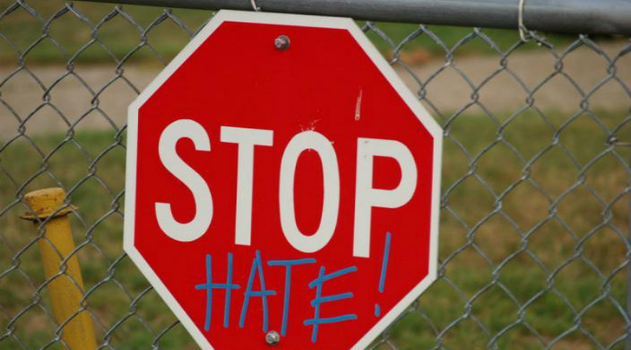 Stop sign spraypainted with the word HATE