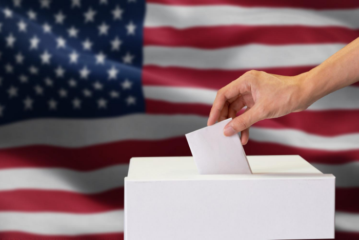 A person putting a ballot in a box in front of an American flag