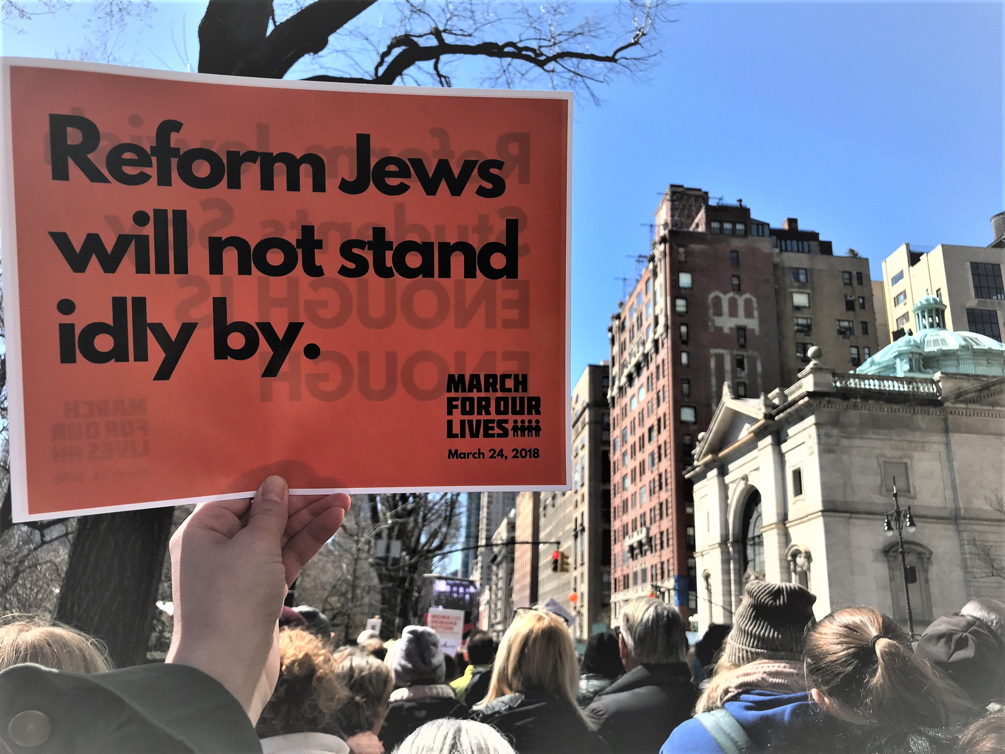 "Person holding a sign saying ""Reform Jews will not stand idly by"""