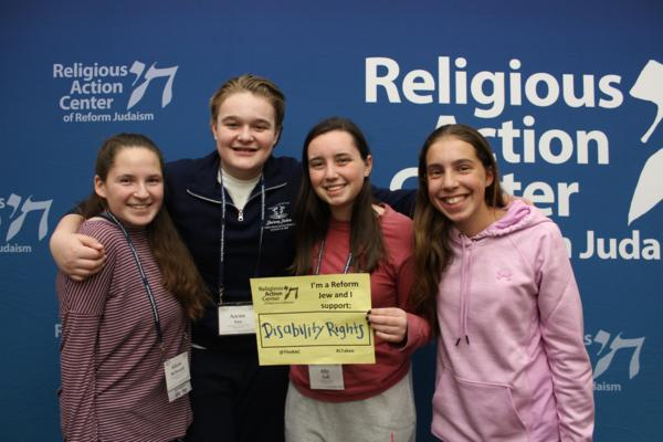 "Four teens pose in front of a RAC banner holding a sign that says ""I'm a Reform Jew and I support Disability Rights"""