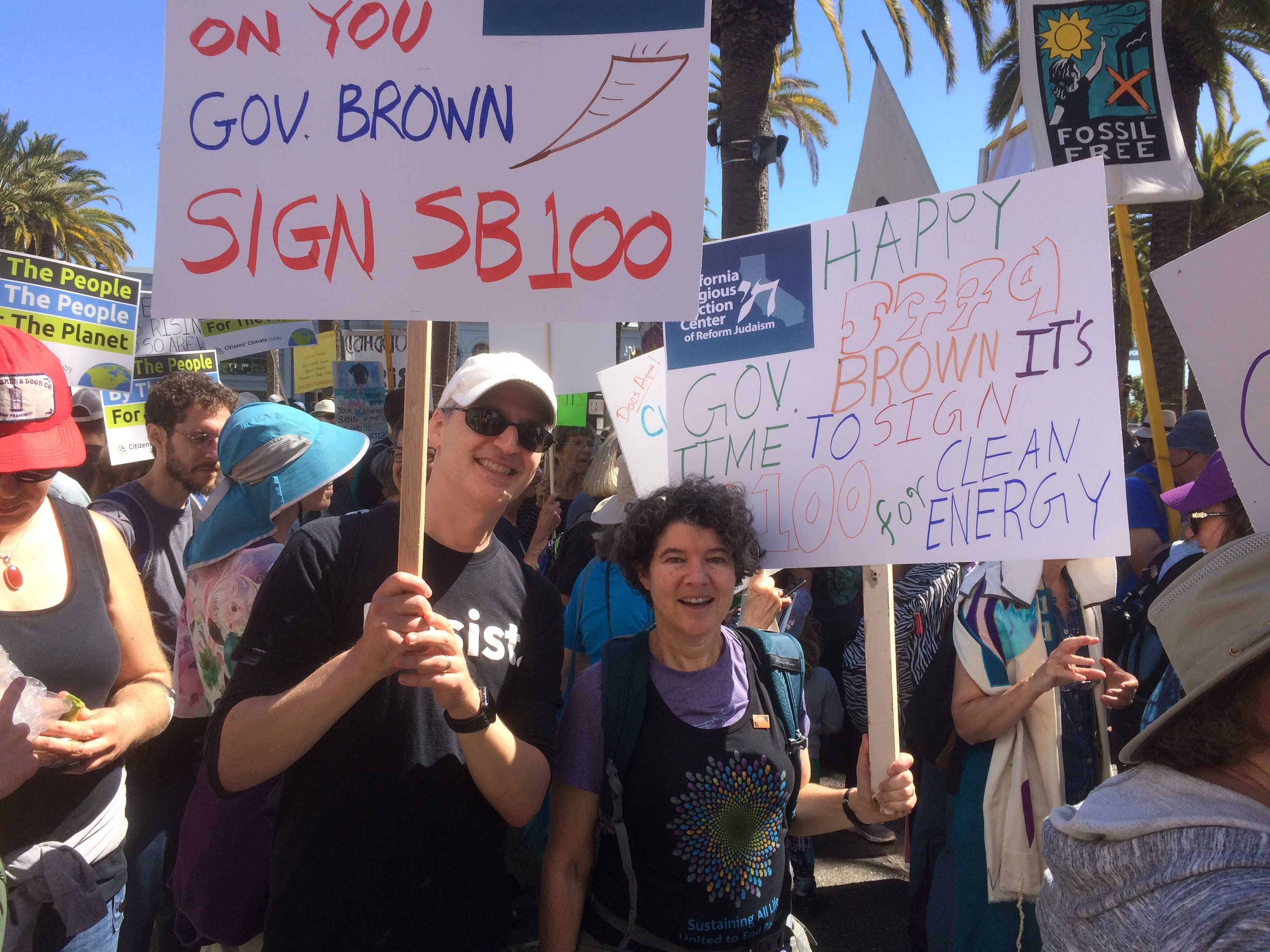 "The authors at a climate change march, holding signs that read ""Happy 5779, Gov. Brown it's time to sign SB 100 for Clean Energy!"""