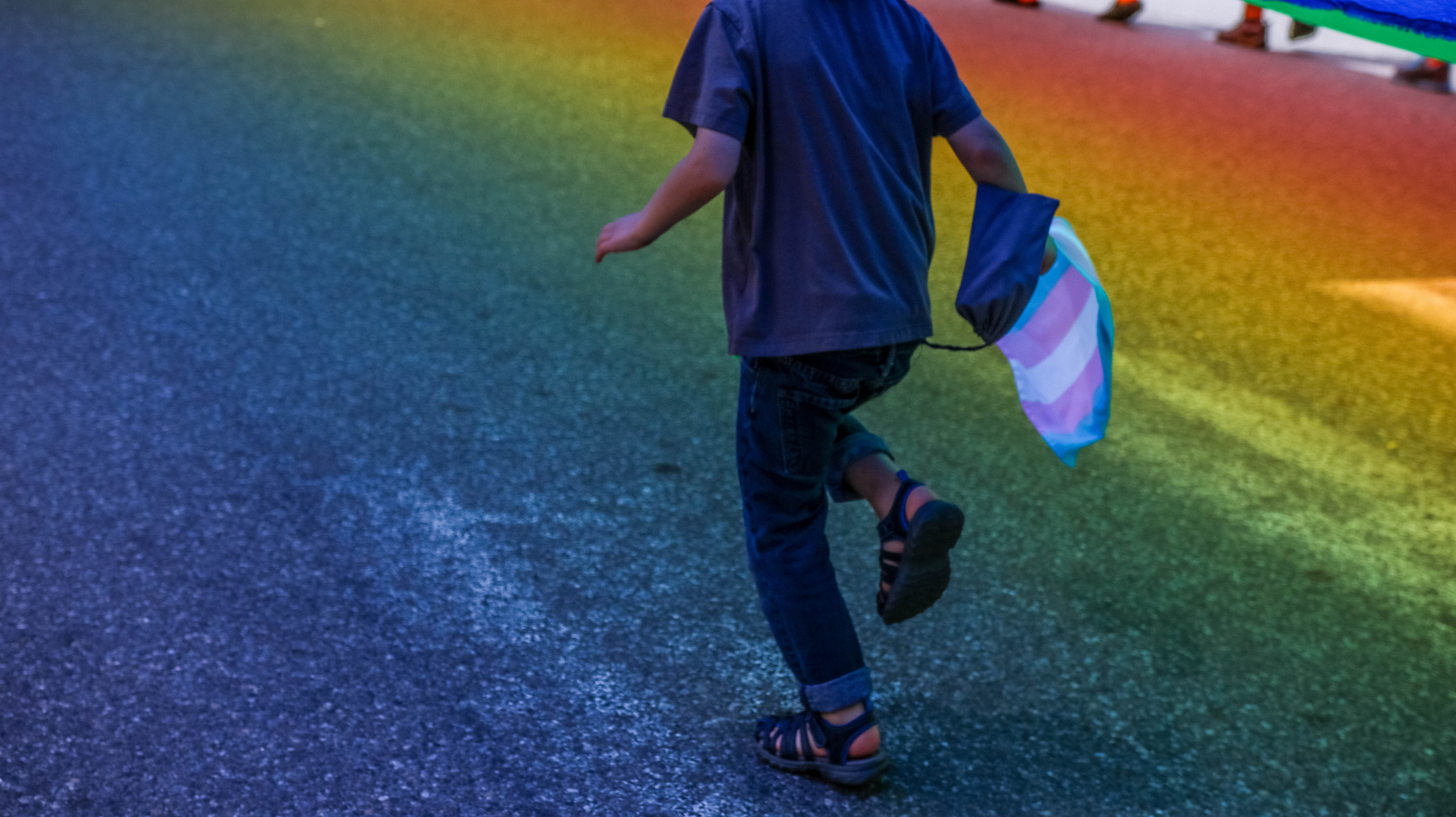Child running through a rainbow reflection holding a transgender rights flag