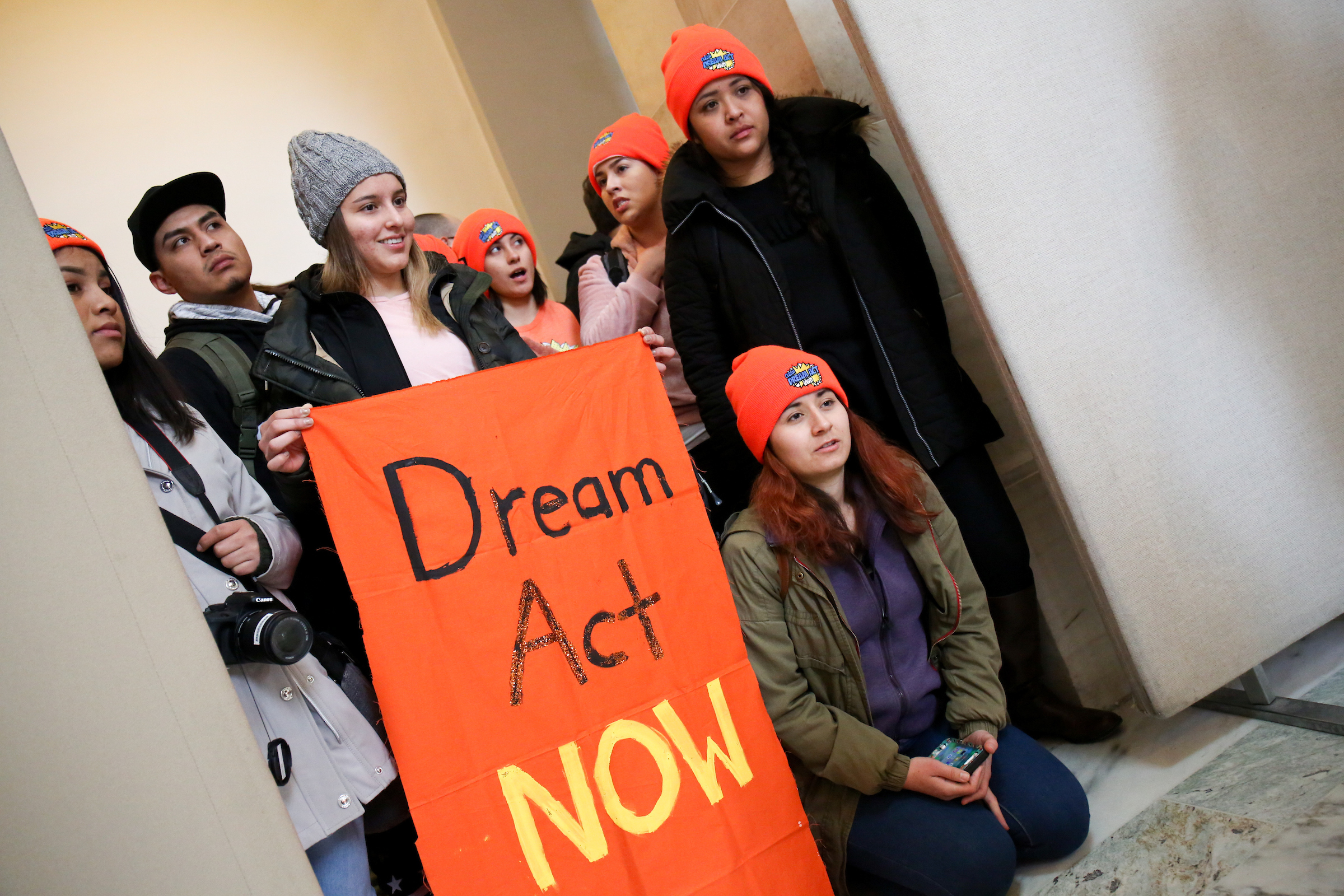 Dreamers holding sign that says DREAM ACT NOW