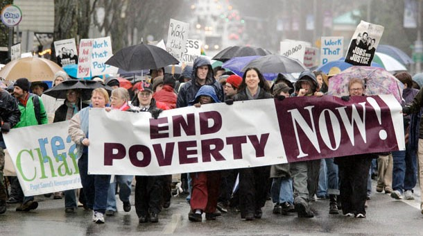 people marching in an anti-poverty rally with a banner