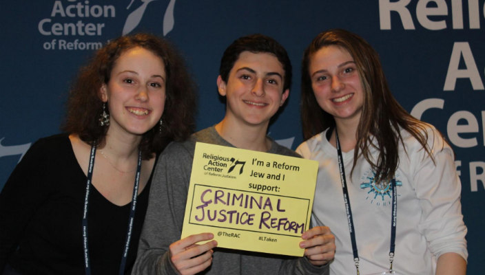 Three teens holding signs in support of criminal justice reform