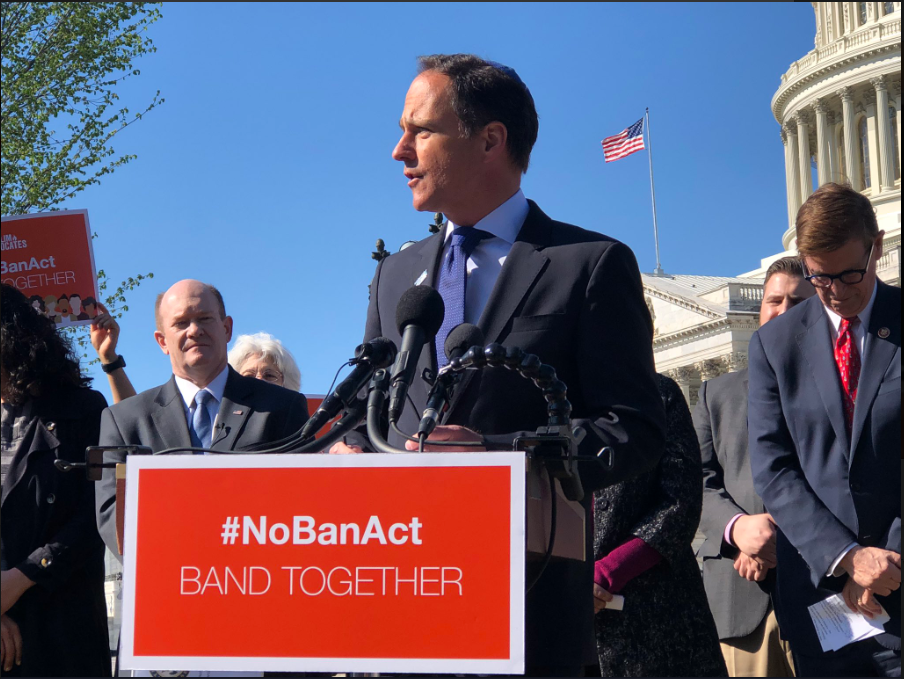 "Rabbi Jonah Pesner speaking at a podium with the sign ""NO BAN ACT"""