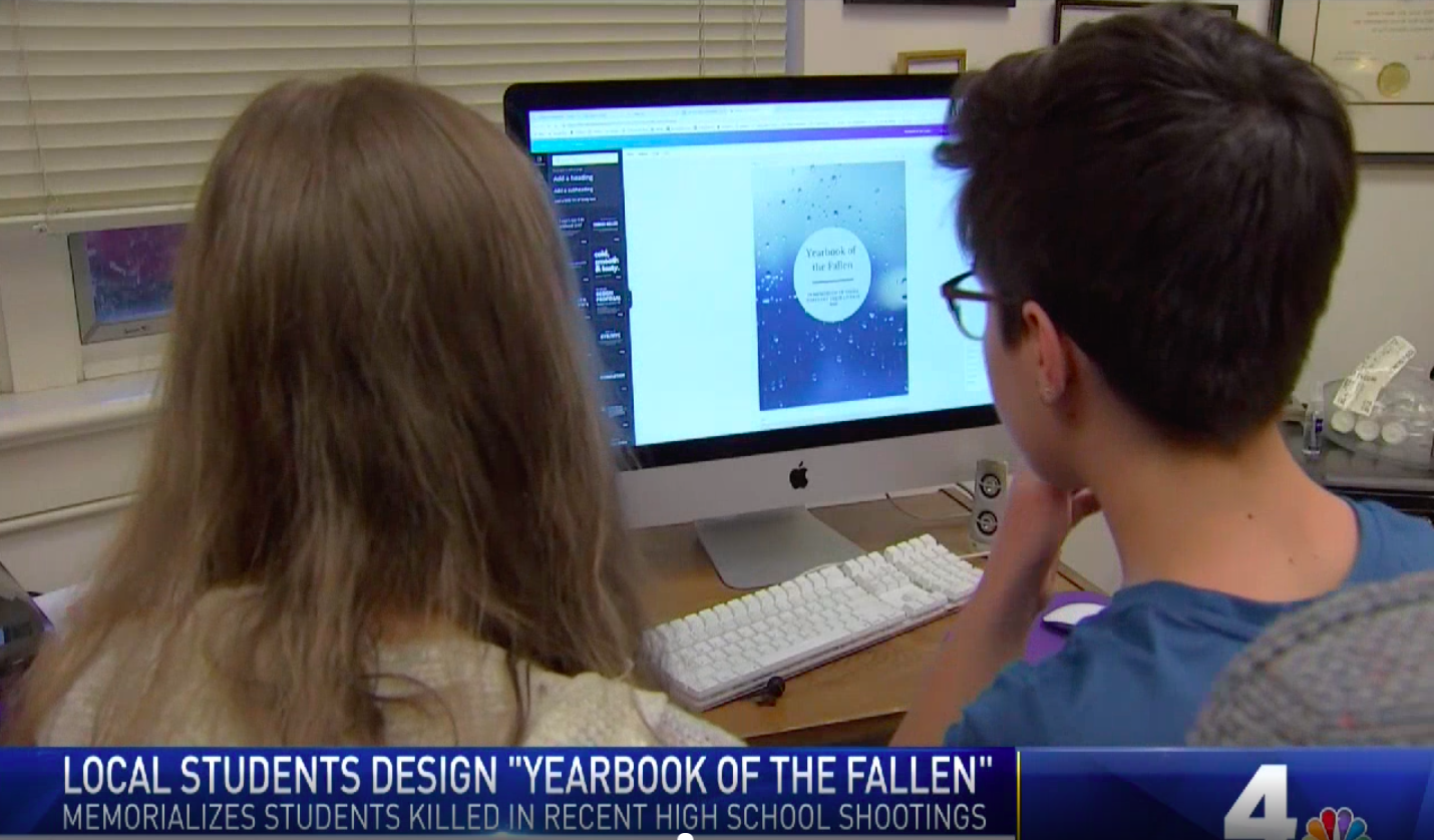 "Shows a video still from a local news story about the yearbook, viewer sees back of two students heads with ""yearbook of the fallen"" displayed on a computer screen"