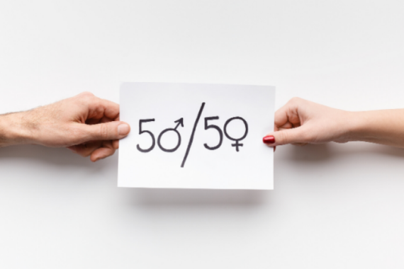 "Hands holding a piece of paper that says ""50/50"""