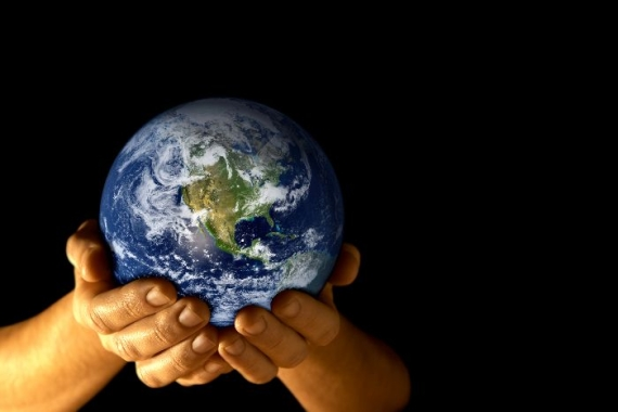 Hands holding planet earth against a black background