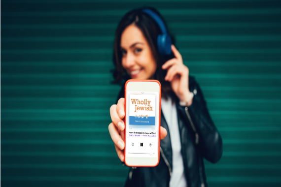 Young woman wearing headphones and listening to Wholly Jewish podcast