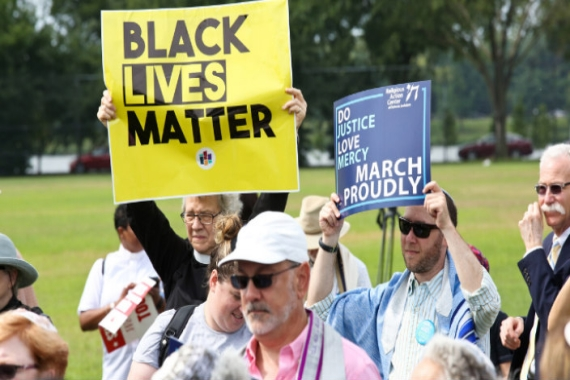 A priest and a rabbi holding signs about justice and Black Lives Matter in a large group of protesters