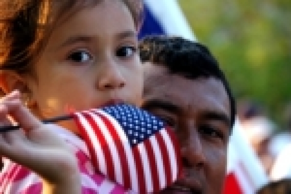 Little girl who adult holding an American flag