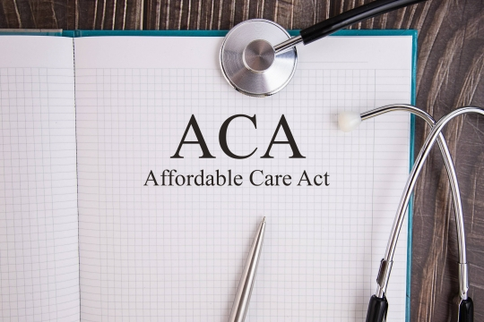 Notepad reading AFFORDABLE HEALTH CARE ACT next to a stethoscope