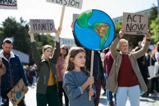 Climate change protest featuring a young girl holding a sign in the shape of planet Earth