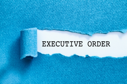The phrase EXECUTIVE ORDER typewritten on white paper beneath a blue folder