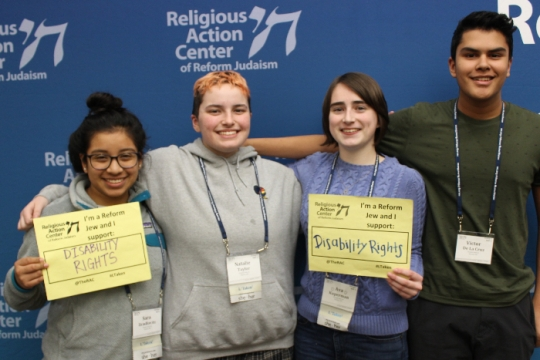 Four teens holding signs that say I AM A REFORM JEW AND I SUPPORT DISABILITY RIGHTS