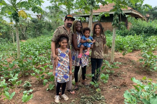 Isaac Hirt Manheimer and wife Ewoenam who founded the UnityEco Village pose among lush greenery with their three young children