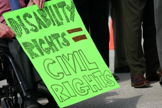 "Person in a wheelchair holding a sign that says ""disability rights=civil rights"""