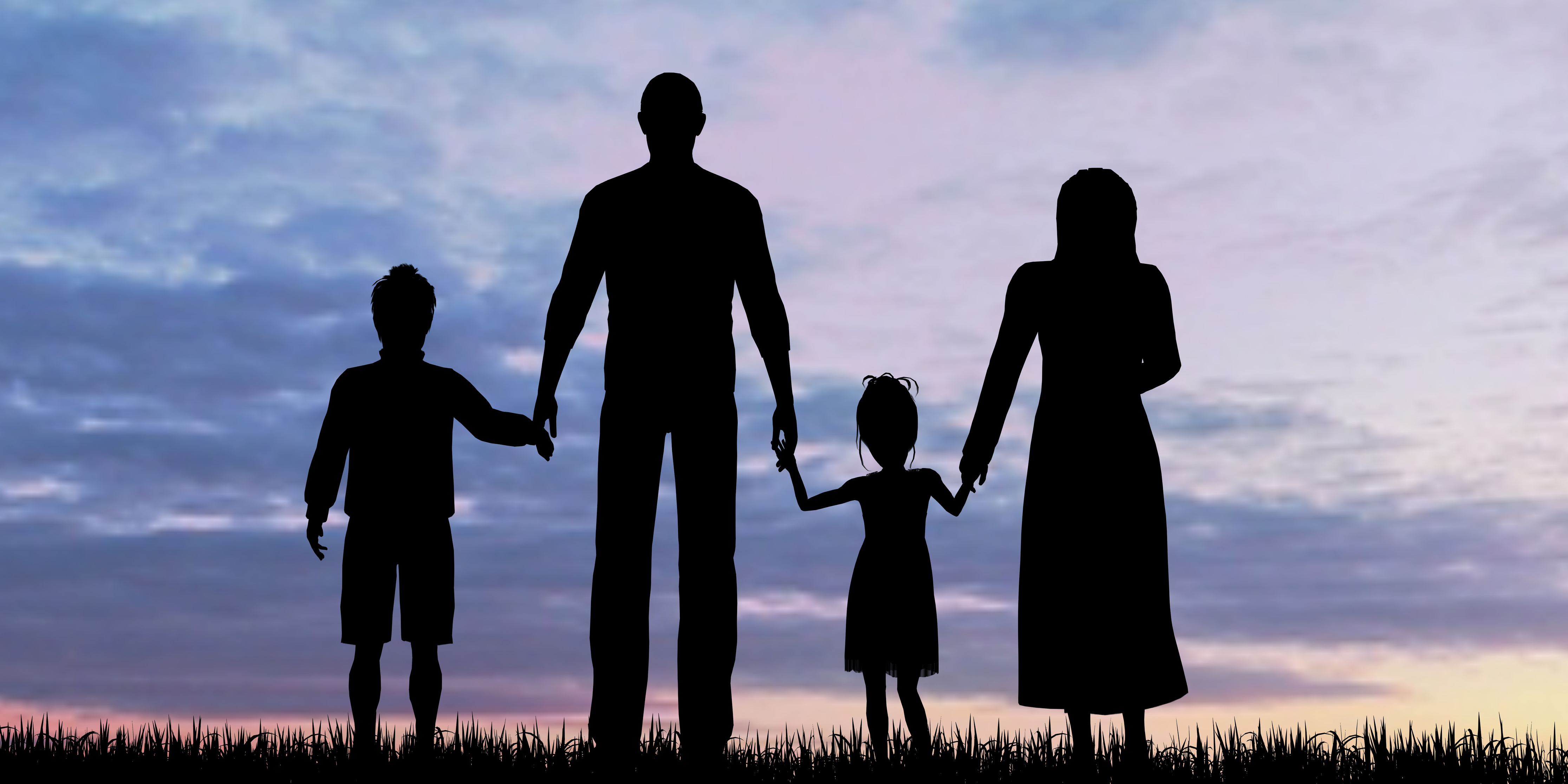 A family standing in silhouette against a sunset