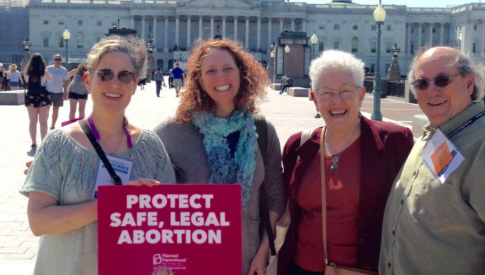 Four individuals holding a sign that says PROTECT SAFE LEGAL ABORTION