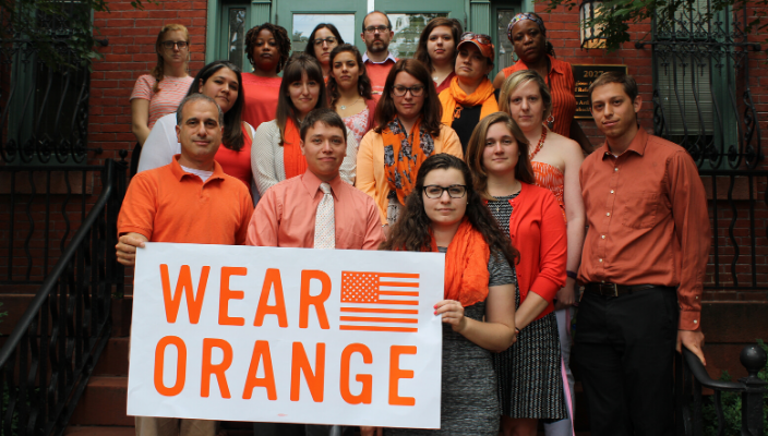 "people wearing orange and holding a sign that says ""wear orange"""